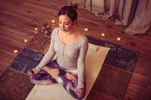 Woman-Meditating-Candles-Yoga-Mat