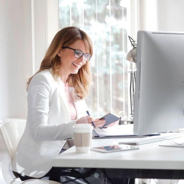 Woman seated at a computer at a virtual organizing session.