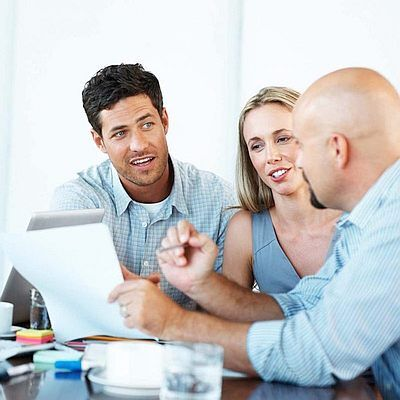 Two men and a woman seated at a table having a business coaching session.